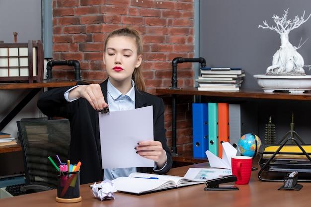 Seria giovane donna seduta a un tavolo e leggendo i suoi appunti sul taccuino in ufficio