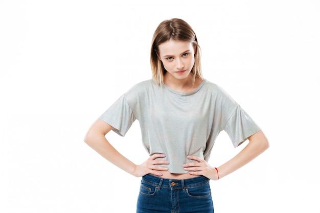 Серьезное положение молодой леди изолированное над белой стеной