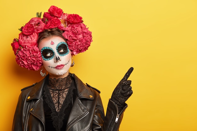 Serious young lady wears dead mask skull makeup, flower wreath, points on free space over yellow wall