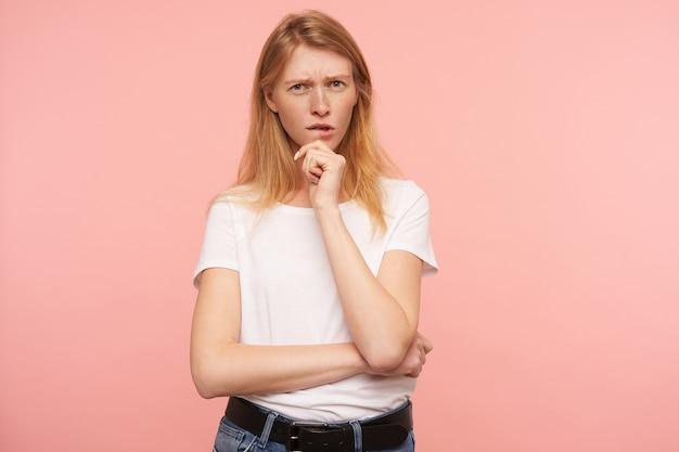 Серьезная молодая милая зеленоглазая рыжая женщина с естественным макияжем хмурит брови, задумчиво смотрит в камеру и держит поднятую руку на подбородке, изолированная на розовом фоне