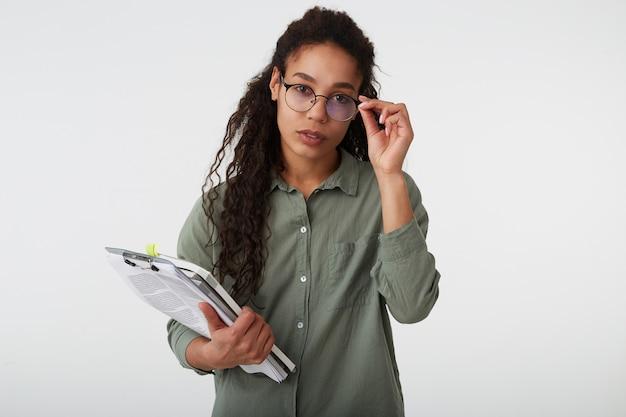 真面目な若い素敵な長い髪の巻き毛の女性は、彼女の眼鏡に手を上げて本を持って、カジュアルな服装で白い背景の上に隔離された暗い肌をしています