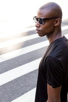Serious young male athlete in black shirt wearing sunglasses looking away