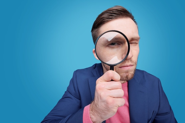 Serious young male detective holding magnifying glass by right eye while standing in isolation