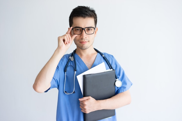 Serious young male doctor holding folder and documents