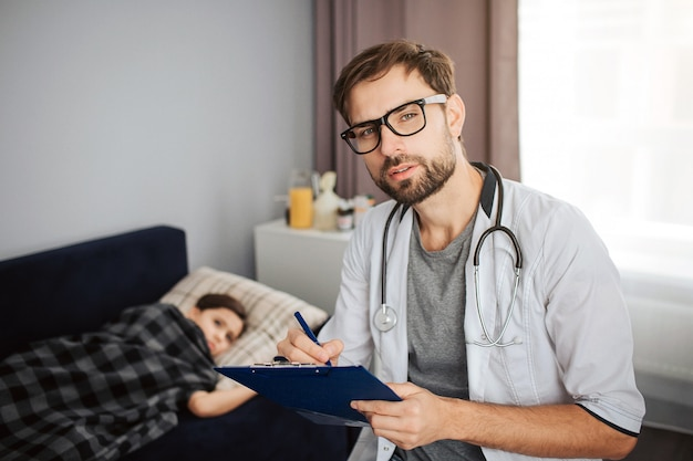 Serious young male doctor look on camera through glasses. his ptient lying on bed. small girl covered with blanket. she sick.