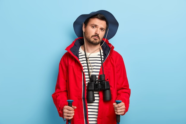 Serious young male hiker has trip in woods, uses trekking sticks, enjoys travel lifestyle, wears binoculars on neck, wears casual hat and red jacket, isolated on blue wall