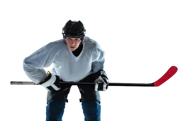 Serious. young male hockey player with the stick on ice court and white wall. sportsman wearing equipment and helmet practicing. concept of sport, healthy lifestyle, motion, movement, action.