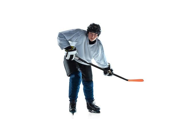 Giovane giocatore di hockey maschio serio con il bastone sul campo da ghiaccio e sul muro bianco