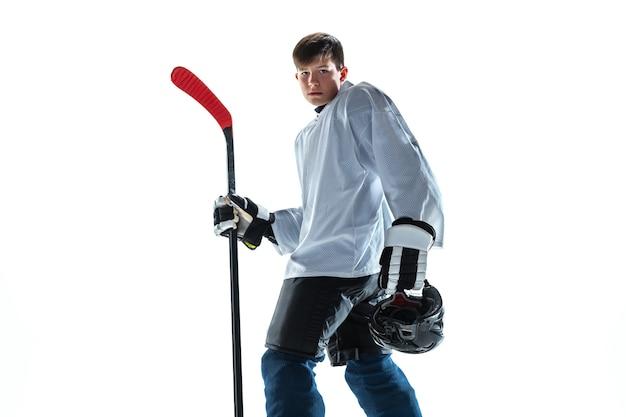 진지한. 아이스 코트와 흰색 배경에 막대기로 젊은 남자 하키 선수. 장비와 헬멧 연습을 착용하는 스포츠맨. 스포츠, 건강한 라이프 스타일, 운동, 운동, 행동의 개념.
