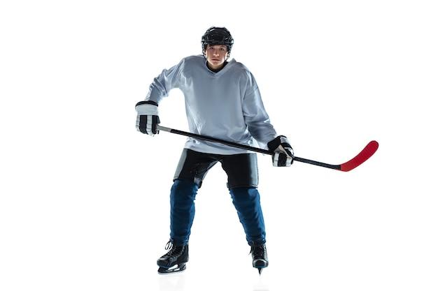 진지한. 얼음 코트와 흰 벽에 막대기로 젊은 남자 하키 선수. 장비와 헬멧 연습을 착용하는 스포츠맨. 스포츠, 건강한 라이프 스타일, 운동, 운동, 행동의 개념.