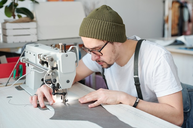 仕事中に針の下に革片を保持しながら電気ミシンを曲げる深刻な若い男性の革細工人