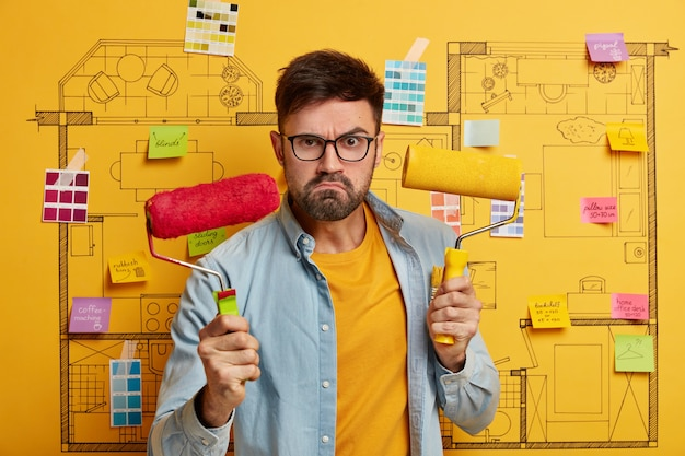 Serious young male stands next to house design sketch ready for renovation