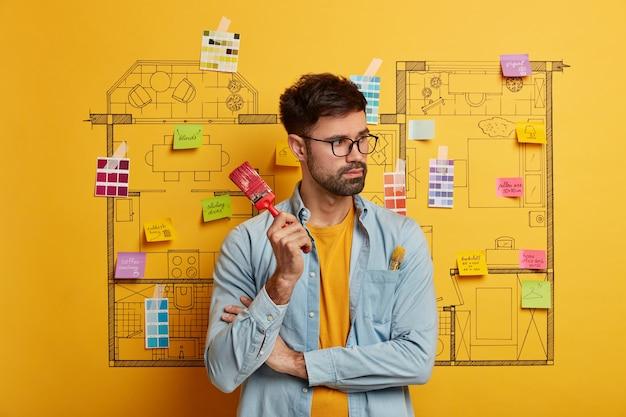 Серьезный молодой мужчина стоит рядом с эскизом дизайна дома, готовым к ремонту