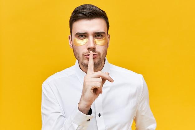 Giovane maschio serio in camicia bianca che tiene l'indice sulle labbra, facendo un gesto di silenzio, chiedendo di tacere e non dire il suo segreto, indossando bende sotto gli occhi mentre è privato del sonno o dopo i postumi di una sbornia