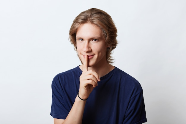 Serious young male with trendy hairstyle, wearing casual t-shirt, showing silence sign, keeping his finger on mouth, asking to keep silence and not telling secret, isolated on white