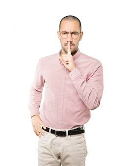 Serious young man asking for silence gesturing with his finger