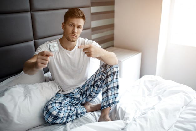 Serious young man on bed in early morning. he hold condom in hand and point on it. mature and sexy.