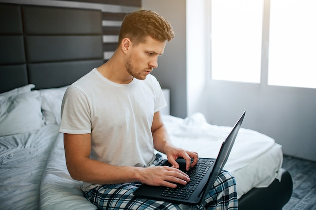 Serious young man in bed this morning. he work at home. guy type on laptop keyboard and look at screen. daylight.