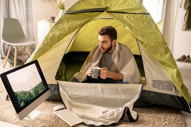 Serious young man under blanket sitting with mug in camping tent and looking at forest picture on monitor in living room, isolation concept