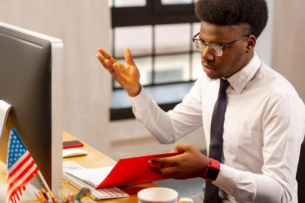 オフィスで働いている間、財務報告をチェックする真面目な青年
