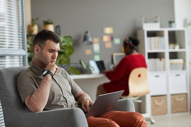 안락의 자에 앉아서 백그라운드에서 노트북을 사용하는 여자와 노트북에서 작업하는 그의 온라인 작업에 집중하는 심각한 젊은 남자
