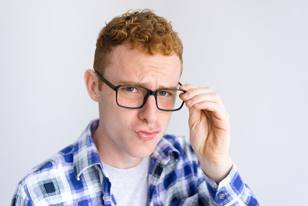 Serious young man frowning and adjusting glasses