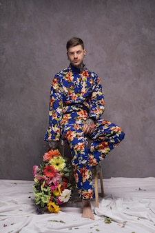 Серьезный молодой человек, держащий букет цветов в руке, глядя на камеру на фоне серой стены