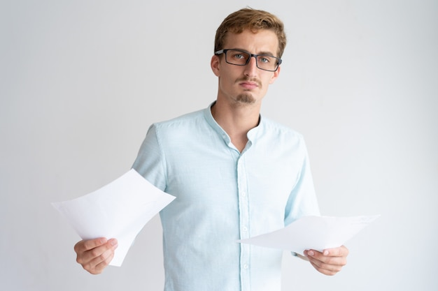 Serious young man holding paper sheets and looking at camera