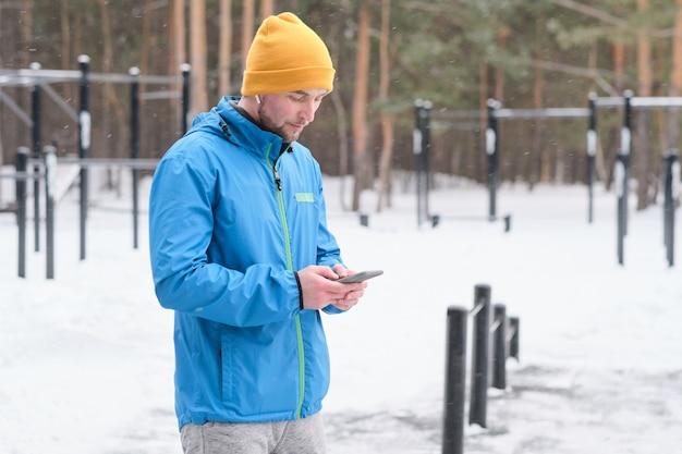 Серьезный молодой человек в яркой шляпе стоит на зимней спортивной площадке и с помощью смартфона делает заметки о тренировках