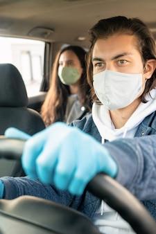 Серьезный молодой человек в тканевой маске и перчатках за рулем клиента такси во время коронавируса