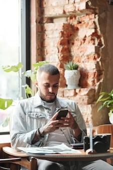 Серьезный молодой человек в джинсовой куртке сидит за столом в кафе-лофте и использует смартфон, отправляя смс