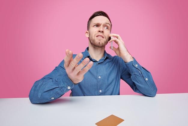 テーブルに座って、ロジックを開発しながらキューブパズルを解くジャケットの真面目な若い男