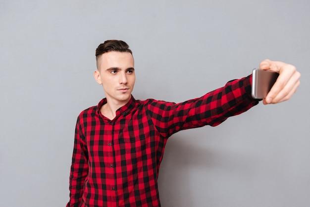 Серьезный молодой человек в рубашке, делая селфи в студии. изолированный серый фон