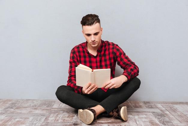Серьезный молодой человек в рубашке сидит на полу и читает книгу. изолированный серый фон