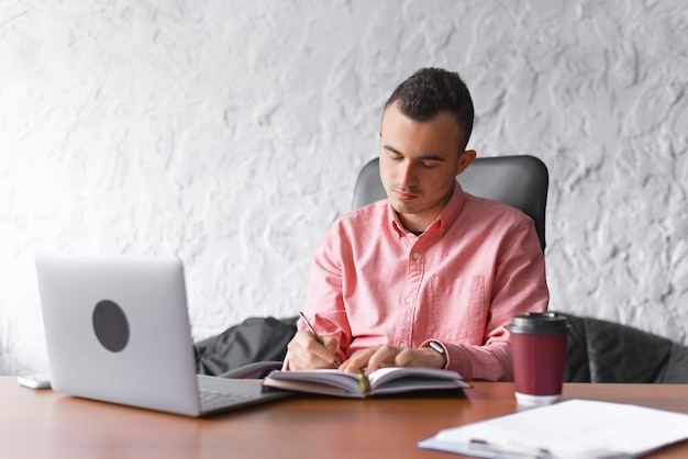 Serious young man is writing in planner or journal at his desk