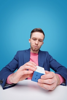 Serious young man in jacket sitting at table and solving cube puzzle while developing logic