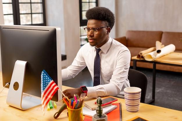 オフィスで働いている間、コンピューターの画面を見ている真面目な青年