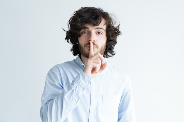 Serious young man making silence gesture and looking at camera