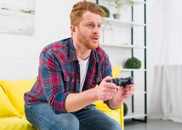 Serious young man playing game with video controller at home