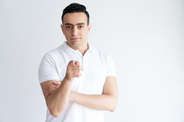 Serious young man pointing at you and looking at camera. guy choosing viewer.