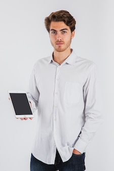 Serious young man posing with tablet