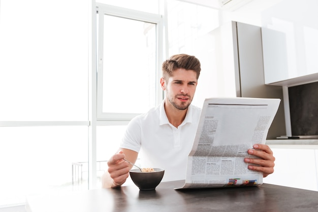Serious young man reading newspaper and eating cereals on the kitchen