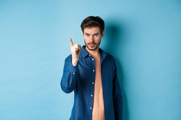 Серьезный молодой человек ругает человека, неодобрительно трясет пальцем, предупреждает или запрещает что-то плохое, стоя на синем фоне.