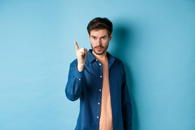 Serious young man scolding person, shaking finger disapprovingly, warn or prohibit something bad, standing on blue background.
