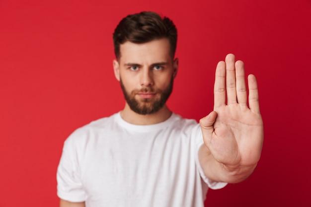 Серьезный молодой человек показывает жест стоп