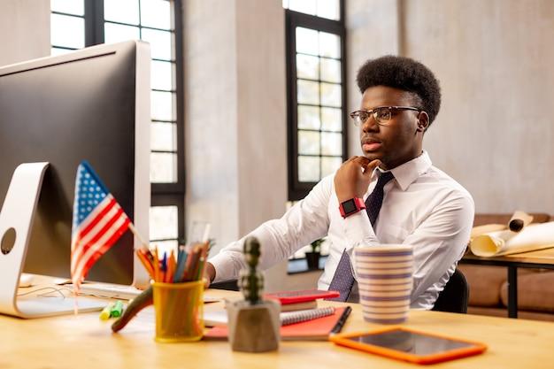 オフィスで働いている間コンピュータの前に座っている深刻な若い男