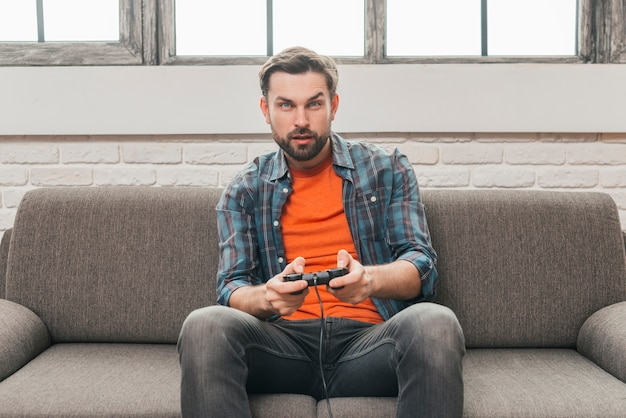 Serious young man sitting on sofa playing video game