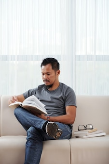 Serious young man sitting on sofa next to stack of books and reading book