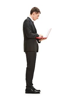 Giovane serio in vestito, cravatta rossa in piedi con il computer portatile in ufficio