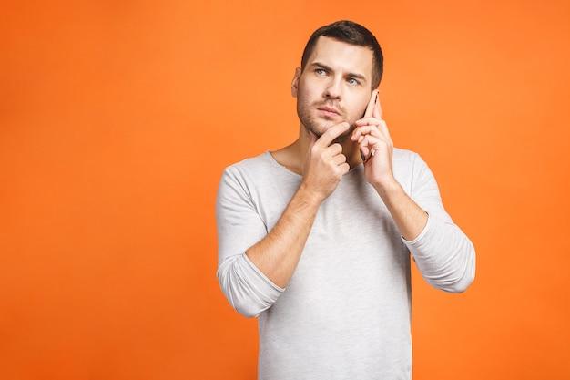Серьезный молодой человек разговаривает по мобильному телефону на оранжевом фоне